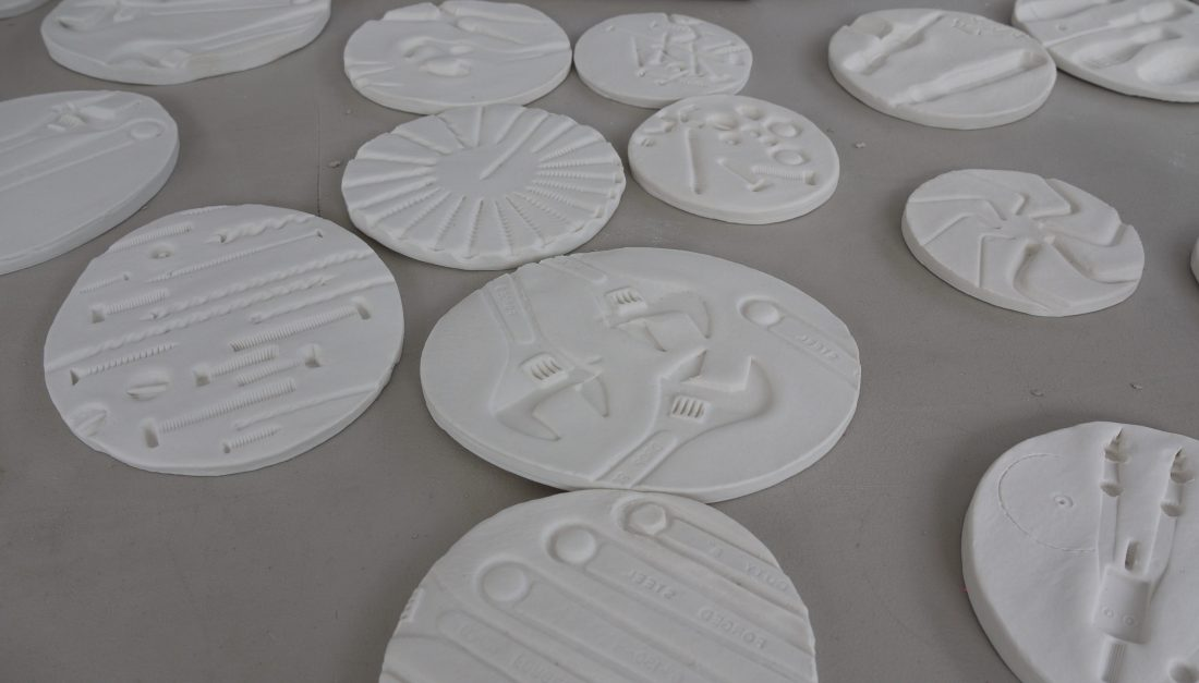 white ceramic circular tiles with patterned imprints of tools