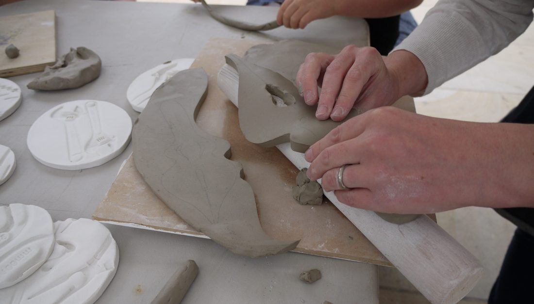 The artist places a slab of clay cut to show a pen nib over a rolling pin to shape it.