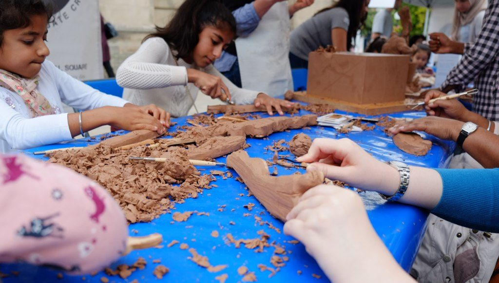 People of various ages sculpt clay using various tools.