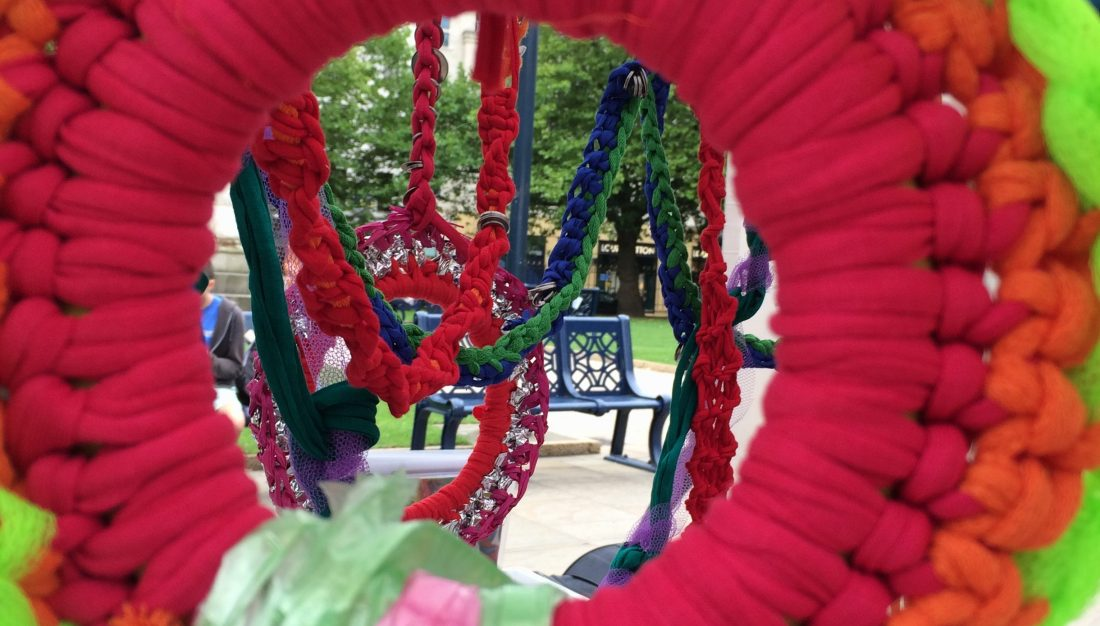 looking through the large-scale brightly coloured chandelier made from knit, crochet and macrame
