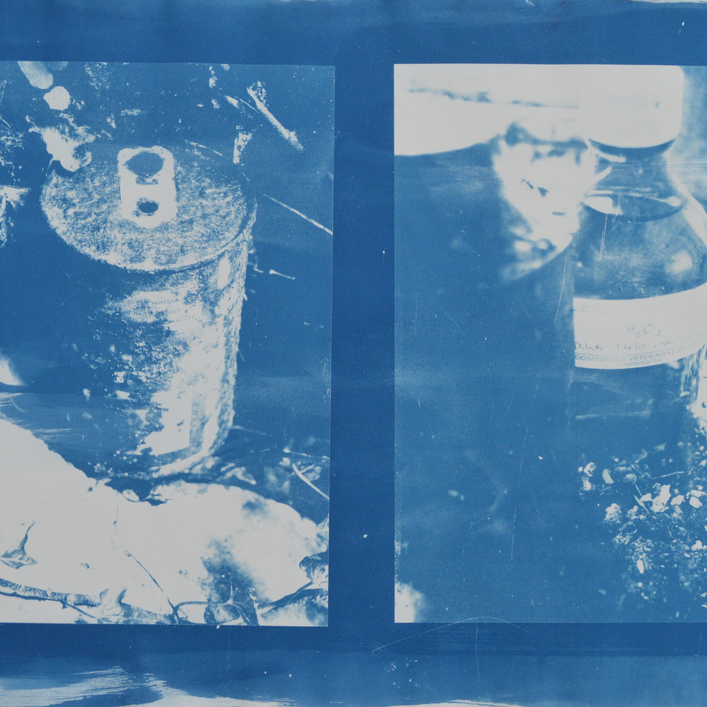 A blue and white cyanotype print showing bottles and cans.