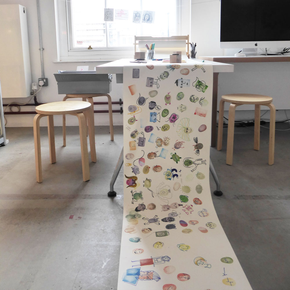 A long sheet of banner paper with coloured fingerprints that are illustrated to look like characters.