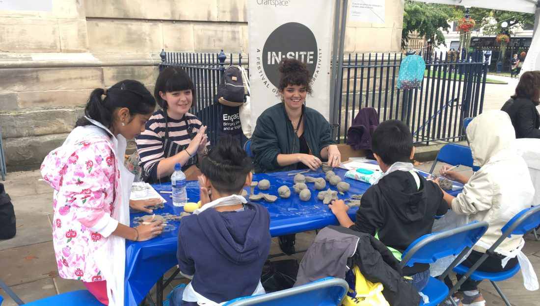 Children rolling clay into balls.