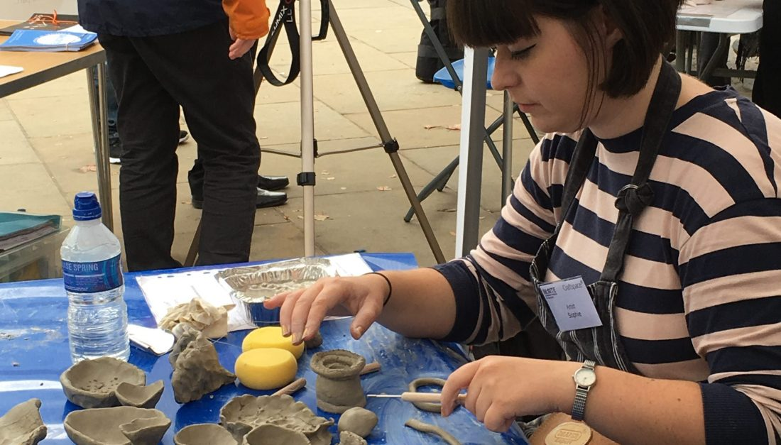 The artist is using tools to mark clay vessel