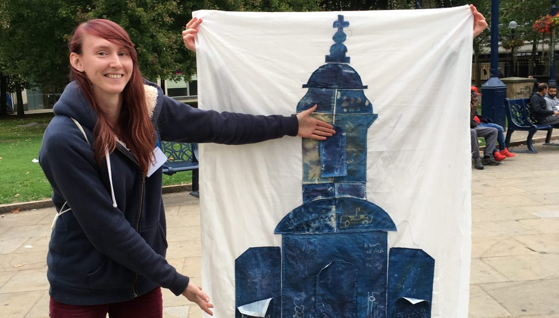 The happy artist is standing next to her textile collaged image of the Cathedral.