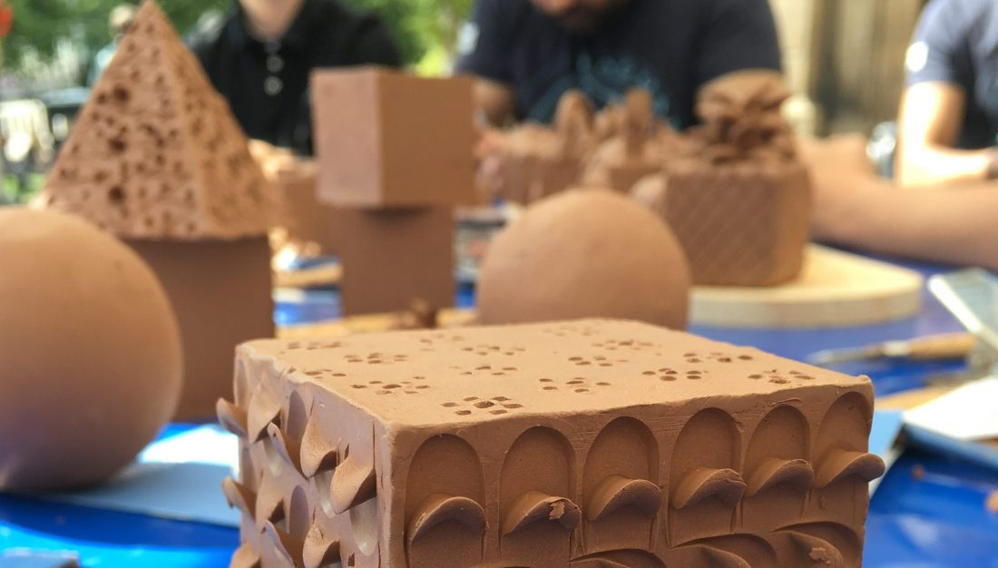 A clay cube that has been carved so that parts protrude around the sides.