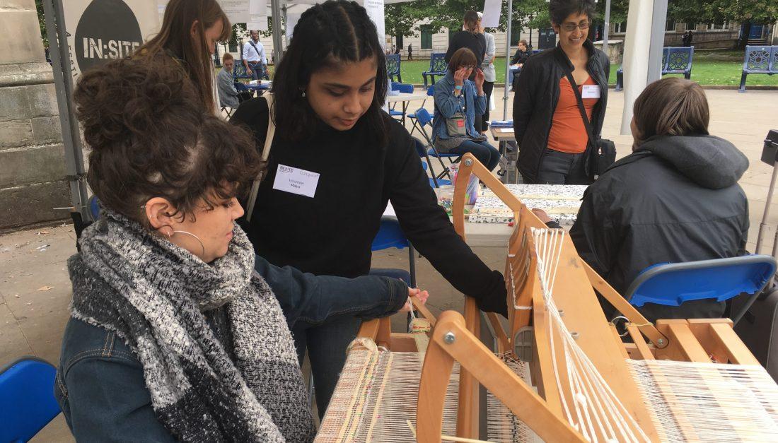 Two volunteers are using weaving loom.