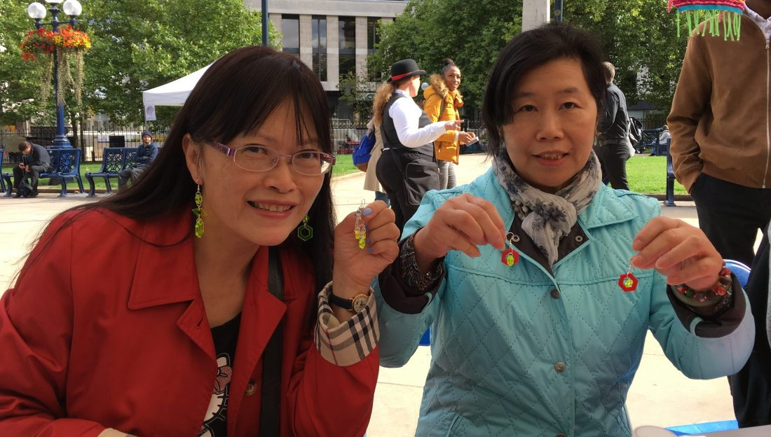 Two women are holding up their hand made earrings.