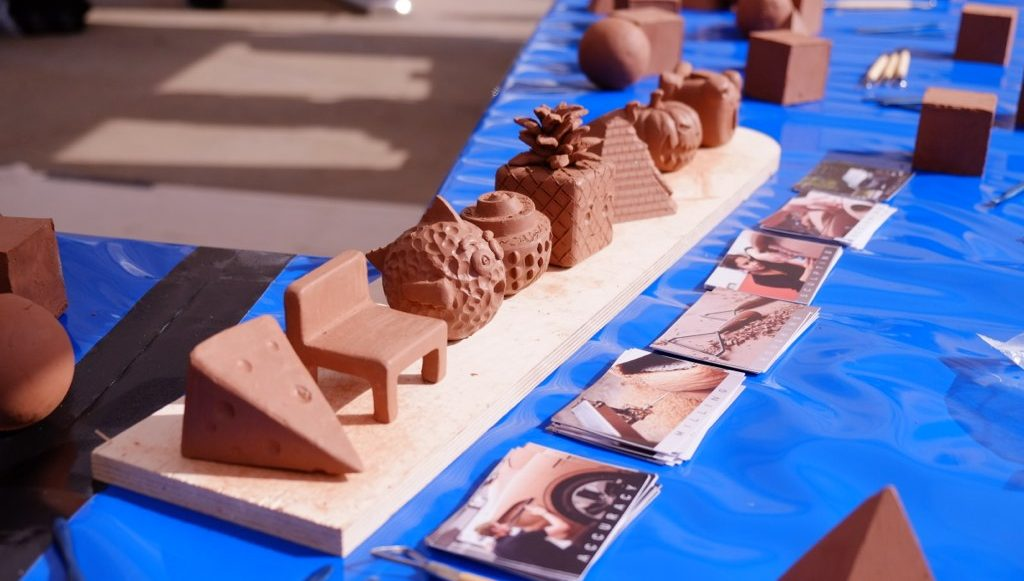 finished sculptures in many different shapes and designs are standing in one line on the table.