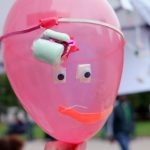 A red balloon with eyes and a mouth.