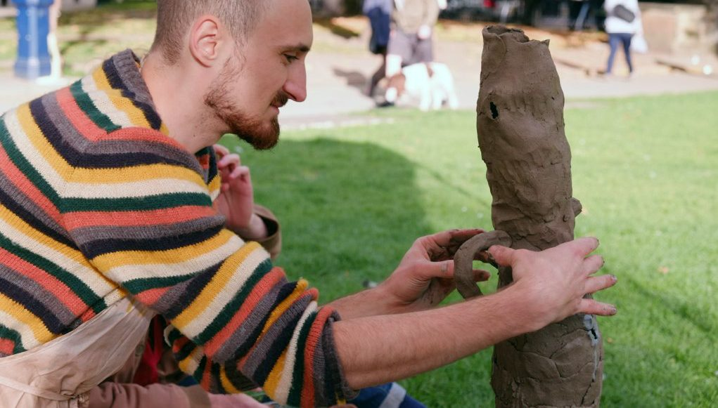 The artist is shaping a tall sculpture with his hands.
