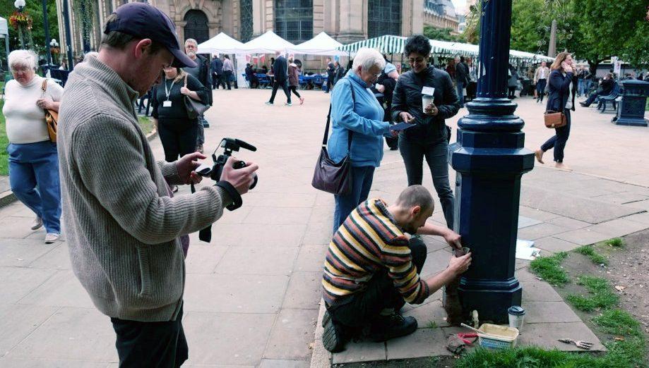 film maker filming artist Marek making clay sculptures on a lamp post