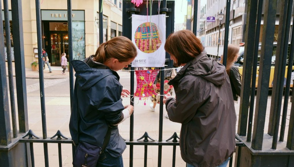 Two women are hanging up the colourful textile piece.