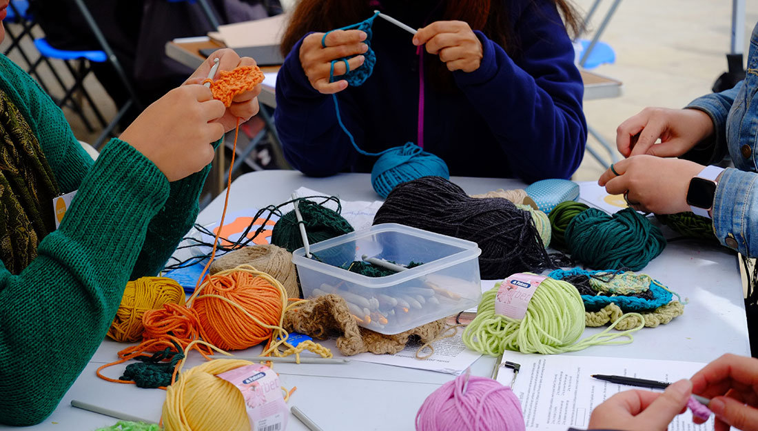 various hands crocheting wool