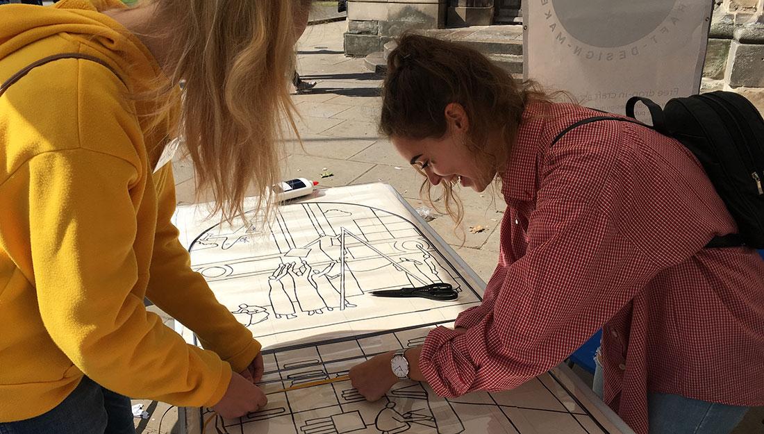 artist and volunteer putting lead tape on artwork
