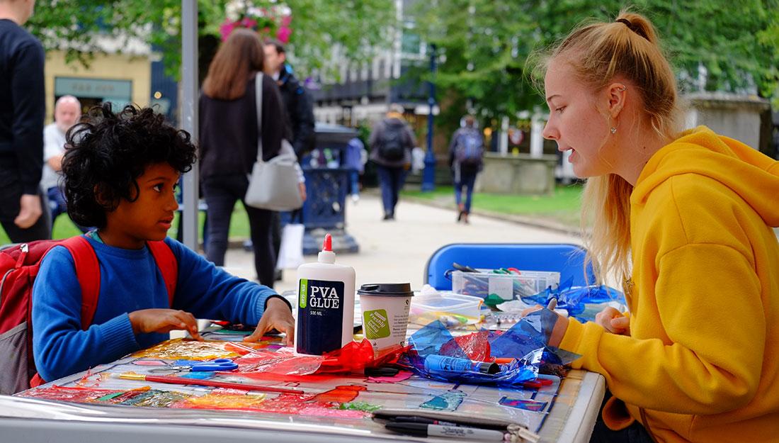 volunteer helps young boy make art work