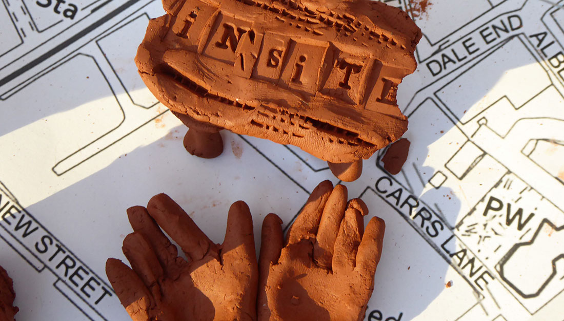 In:Site stamped in clay with clay hands on a map