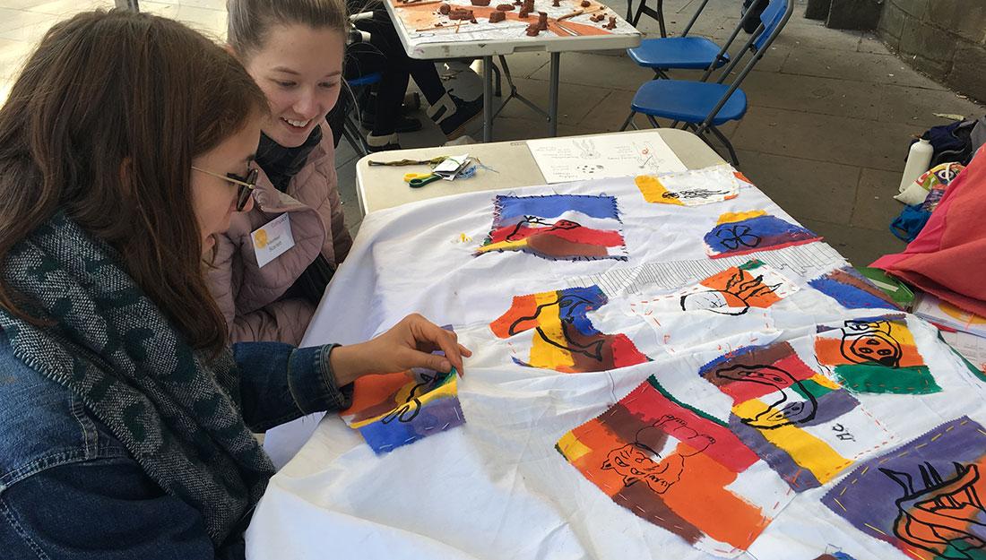 participants stitch motifs onto fabric