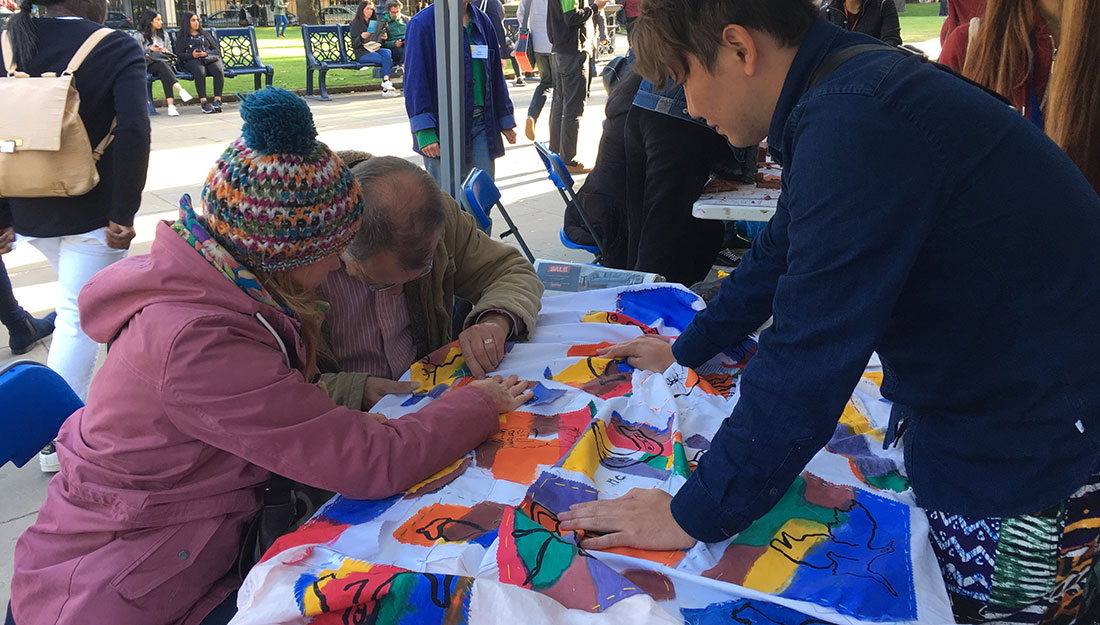 artist and volunteer help participant stitch motif to fabric