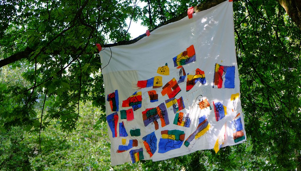white sheet with colourful applique motifs sewn onto it hanging from a tree